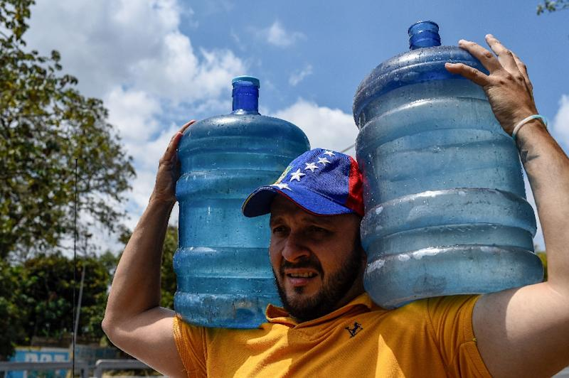 A man carries drums with water he collected from a stream at the Wuaraira Repano mountain, also called El Avila, in Caracas on March 13, 2019 (AFP Photo/Federico Parra)
