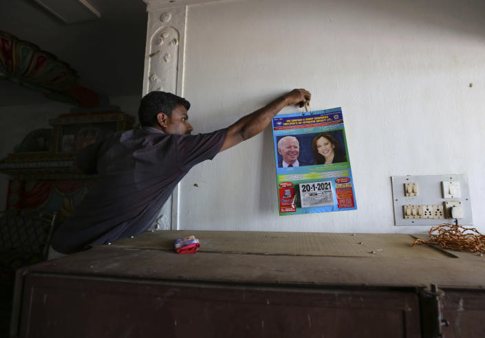 A villager hangs a calendar featuring photographs of U.S. President-elect Joe Biden and Vice President-elect Kamala Harris inside a wedding hall in Thulasendrapuram, the hometown of Harris' maternal grandfather, south of Chennai, Tamil Nadu state, India, Tuesday, Jan. 19, 2021. The inaugural ceremony for Biden and Harris is scheduled be held Wednesday. (AP Photo/Aijaz Rahi)