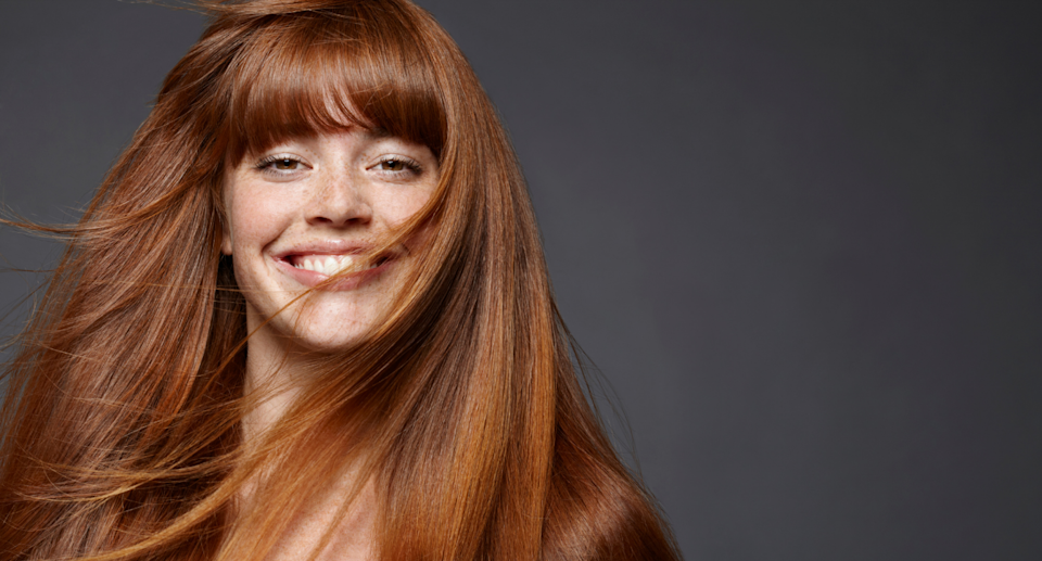 red head model with freckles smiling with hair blowing in her face