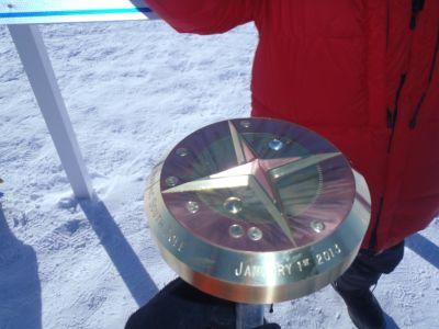 Dr. Ross snaps a picture of the official marker of the South Pole.