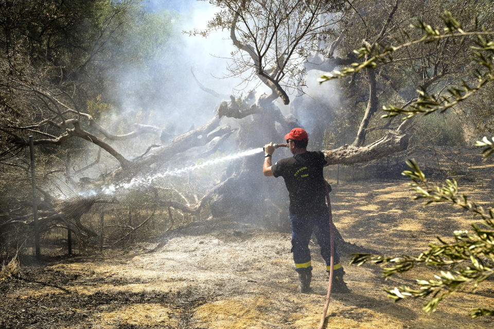 PATRAS, GREECE - AUGUST 01: Firefighters continue to tackle a wildfire near the village of Ziria on August 1, 2021 in Ziria, Greece. Nearly 300 firefighters, two water bomber planes and five helicopters were battling to put out a forest fire in Greece that has so far destroyed around 20 homes and injured eight people, authorities said. (Photo by Milos Bicanski/Getty Images)