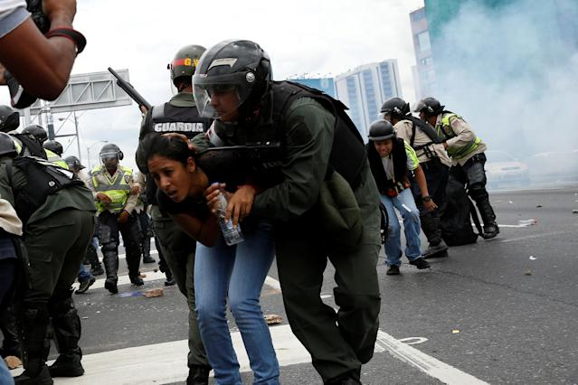 <p>A Venezuelan National Guardsman covers a woman as they run away from tear gas during a rally to demand a referendum to remove President Nicolas Maduro, in Caracas, June 7, 2016. (Reuters/Carlos Garcia Rawlins) </p>