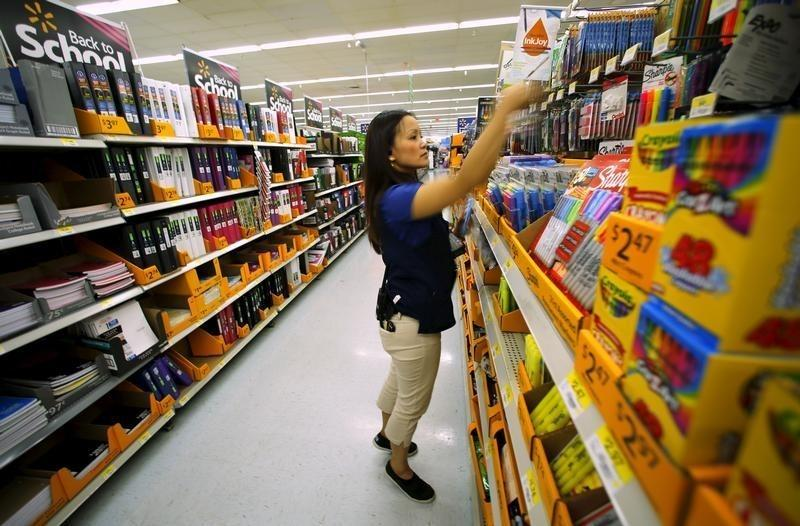 Walmart department manager Karren Gomes helps stock shelves with school supplies as the retail store prepare for back to school shoppers in San Diego, California