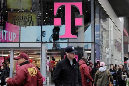 FILE PHOTO: Pedestrians walk past a T-Mobile store in New York
