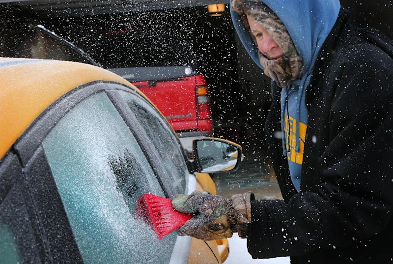 Landon Porter, 15, scrapes the ice off his mother's car outside his home Sunday, March 2, 2014, in St. Charles, Mo. A winter storm packing high winds, ice and heavy snow threatened to create hazardous driving conditions across Kansas and Missouri, accompanied by wind chills approaching 25 below zero in some areas. (AP Photo/St. Louis Post-Dispatch, David Carson)