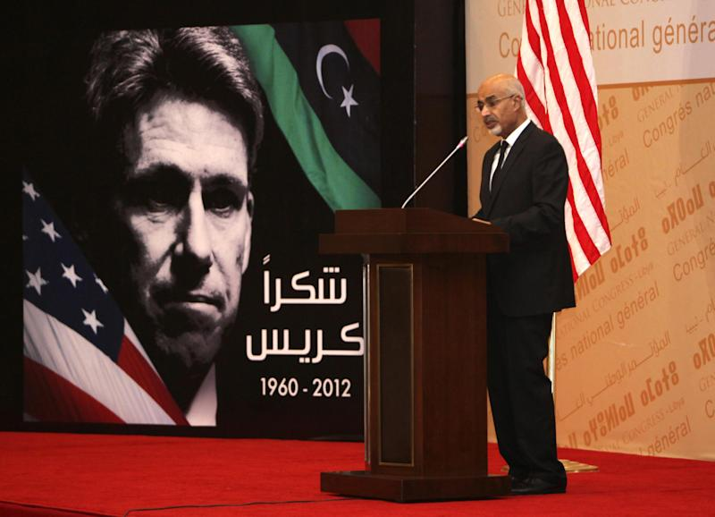"""Libyan President Mohammed el-Megarif speaks during a memorial service in Tripoli, Libya, Thursday, Sept. 20, 2012, for U.S. Ambassador to Libya, Chris Stevens, and three consulate staff killed in Benghazi on Sept. 11. The deputy U.S. secretary of state has met senior Libyan officials in Tripoli and attended a memorial service for the American ambassador and three consulate staffers killed in an attack last week. William Burns is the most senior US official to visit Libya in the aftermath of the Sept. 11 attack on the consulate in Benghazi and comes as Washington is still working to piece together how its top diplomat there, Ambassador Chris Stevens, was killed. Arabic on the poster reads, """"thank you, Chris."""" (AP Photo/Abdel Magid al-Fergany)"""