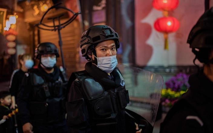 Security guards patrol on a street outside of a shopping mall complex in Beijing - NICOLAS ASFOURI , AFP