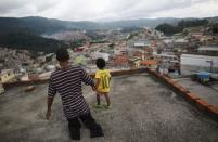 Igor, 6, and his handicapped uncle Claudio, 43, walk on the roof of their house in Brasilandia slum, in Sao Paulo February 10, 2015. REUTERS/Nacho Doce