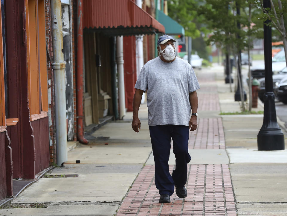 Vietnam veteran Robert Ingram, 74, walks down West Broad Street in downtown Sparta hit hard by COVID-19 on Wednesday, May 20, 2020. Ingram's aunt survived coronavirus at Sparta Health and Rehab where multiple residents have died.(Curtis Compton/Atlanta Journal-Constitution via AP)