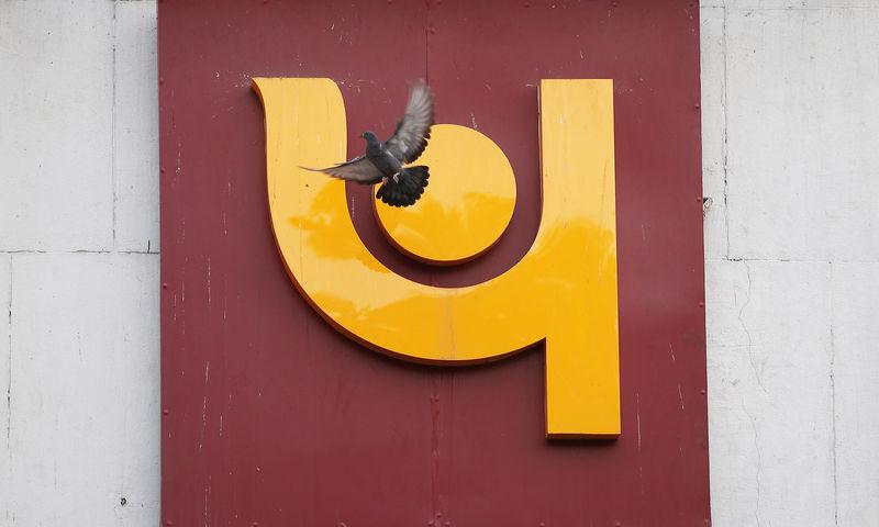 A pigeon flies past the logo of Punjab National Bank outside a branch of the bank in New Delhi