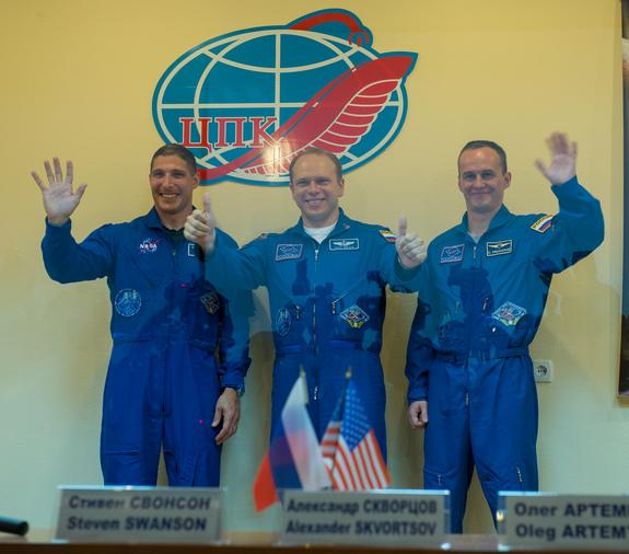 Expedition 37 NASA Flight Engineer Michael Hopkins, far left, Soyuz Commander Oleg Kotov and Russian Flight Engineer Sergey Ryazanskiy, far right, wave and give two thumbs up following a press conference held at the Cosmonaut Hotel, on Tuesday,