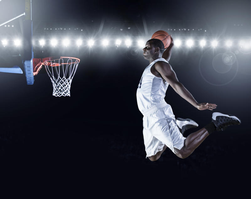 Basketball player dunking basketball