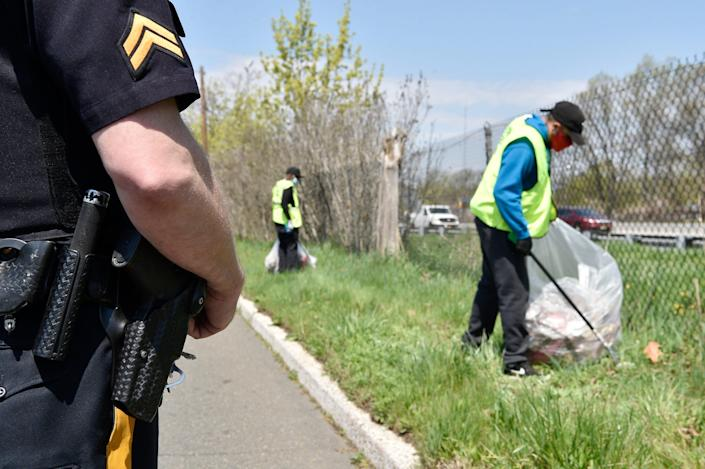 Two men pay off community service time picking up garbage as part of the Sheriff's Labor Assistance Program, SLAP, along River Road in Clifton, N.J., on Tuesday.
