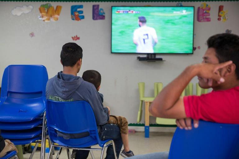 A father and son seeking asylum watch a World Cup match at a Catholic Charities relief center in McAllen, Texas, near the border with Mexico