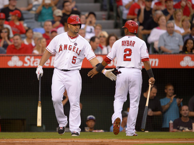 Los Angeles Angels' Erick Aybar, right, is congratulated by Albert Pujols after scoring on a single by J.B. Shuck during the second inning of their baseball game against the St. Louis Cardinals, Tuesday, July 2, 2013, in Anaheim, Calif. (AP Photo/Mark J. Terrill)