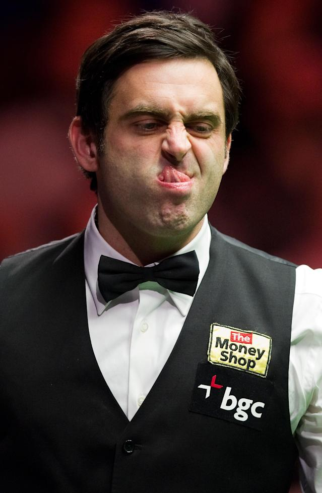 Ronnie O'Sullivan of England reacts after playing a shot against Ding Junhui of China during the first round match in the BGC Masters snooker tournament at Alexandra Palace in north London on January 15, 2012. O'Sullivan went on to win the match 6-4. AFP PHOTO / LEON NEAL (Photo credit should read LEON NEAL/AFP/Getty Images)