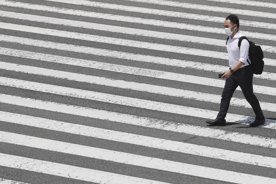 A man wears face mask to help protect against the spread of the new coronavirus passes on a crosswalk in Tokyo, Tuesday, Aug, 4, 2020. (AP Photo/Koji Sasahara)