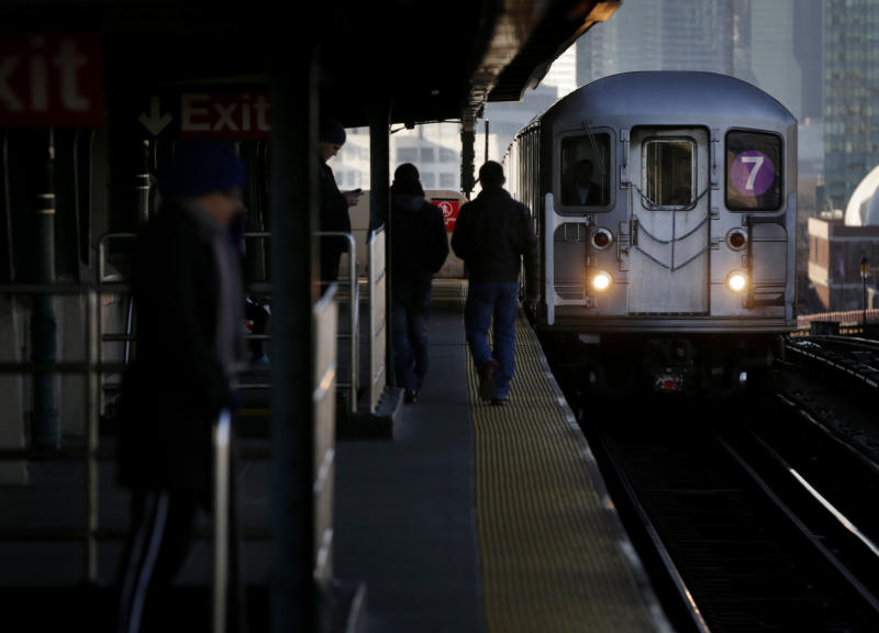 Commuters walk on the platform as a train enters the 40th St-Lowry St Station, where a man was killed after being pushed onto the subway tracks, in the Queens section of New York, Friday, Dec. 28, 2012. Police are searching for a woman suspected of pushing the man and released surveillance video Friday of her running away from the station. (AP Photo/Seth Wenig)