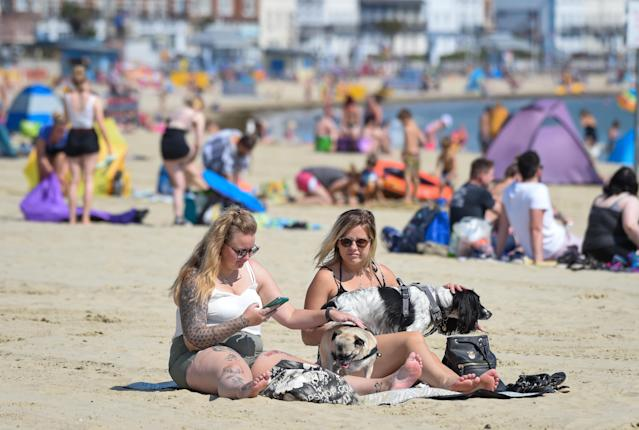 Visitors enjoy the hot weather on the beach in Weymouth (Picture: Getty)
