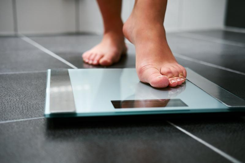 Female bare feet with weight scale in the bathroom