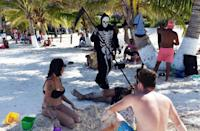 A young man disguised as death walks on the beach of Puerto Morelos, Mexico, inviting tourists and locals to return home, as the beaches are still closed to visitors