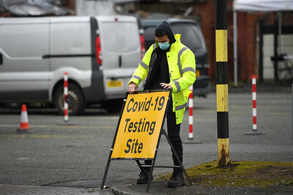 A NHS 'test and trace' worker moves a sign  at a drive through/walk up Covid-19 testing facility in Moston, geater Manchester on February 19, 2021, as a handful of cases of a Covid-19 'variant of concern' has surfaced in the area. (Photo by Oli SCARFF / AFP) (Photo by OLI SCARFF/AFP via Getty Images)