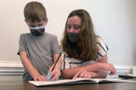 Emily Goss goes over school work at the kitchen table with her five-year-old son inside their Monroe, N.C., home on Monday, Sept. 13, 2021. The Goss' have decided to homeschool Berkeley after the Union County school district chose not to implement a mask mandate for children. (AP Photo/Sarah Blake Morgan)