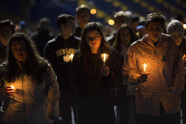 <p>Led by high school students, mourners walk around the track of the football field with candles during a community vigil at Newtown High School for the victims of last week's mass shooting at Marjory Stoneman Douglas High School in Parkland, Fla., Feb. 23, 2018 in Newtown, Conn. Newtown is home to Sandy Hook Elementary School, where 26 people, 20 of them children, were killed in a mass shooting in 2012. (Photo: Drew Angerer/Getty Images) </p>