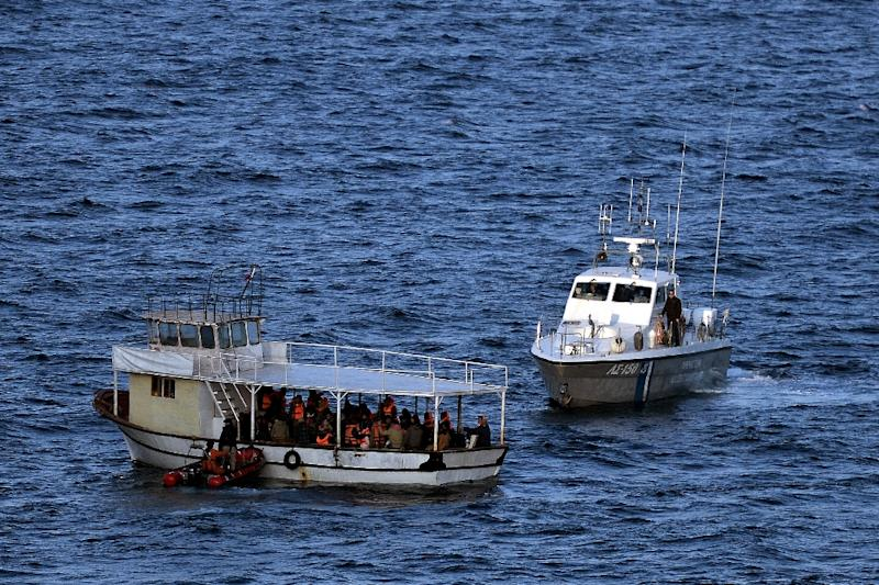 A boat carrying refugees and migrants is escorted by Greek coast guards off the coast of the Greek Lesbos island after crossing the Aegean Sea from Turkey on November 7, 2015