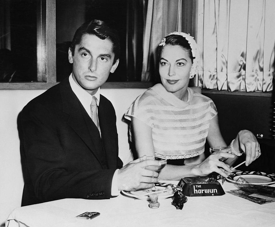 <p>Gardener, wearing a bonnet-style hat and striped dress sits with Bob Evans at the Harwyn Club in New York, after filing for divorce from Sinatra in Mexico City the day before. </p>