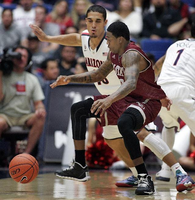 New Mexico States' Daniel Mullings, front, and Arizona's Nick Johnson, back, scramble for control of a loose ball in the first half of an NCAA college basketball game on Wednesday, Dec. 11, 2013 in Tucson, Ariz. (AP Photo/John MIller)