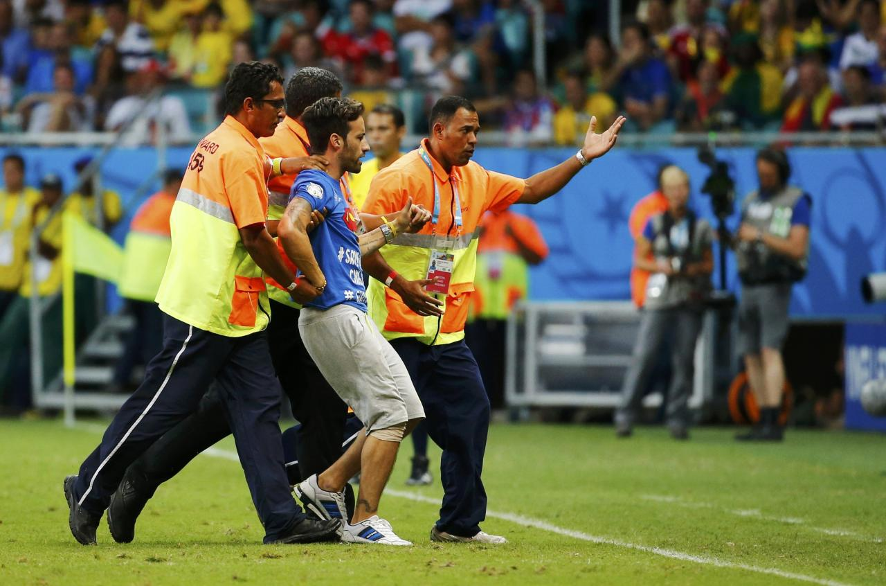 A pitch invader is escorted away by stewards during the 2014 World Cup round of 16 game between Belgium and the U.S. at the Fonte Nova arena in Salvador July 1, 2014. REUTERS/Yves Herman (BRAZIL - Tags: SOCCER SPORT WORLD CUP)