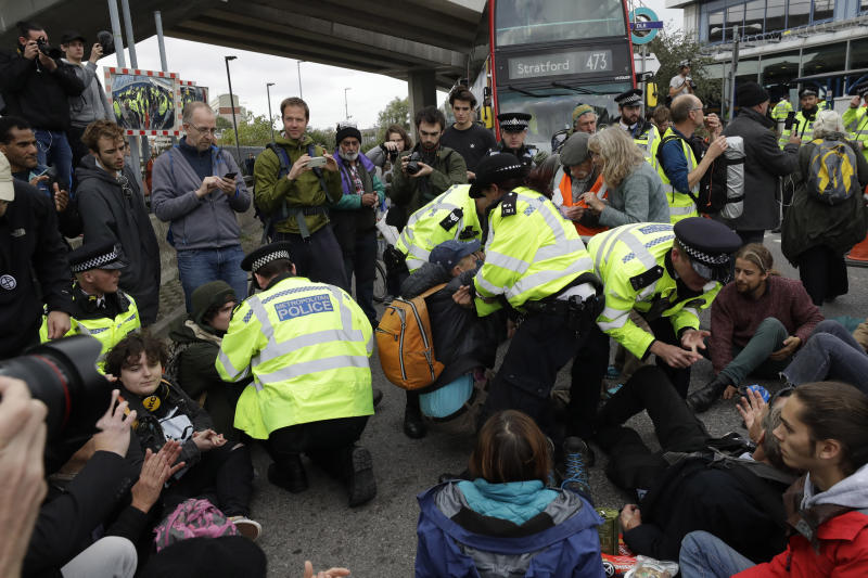 Extinction Rebellion climate change protesters block a road outside City Airport in London, Thursday, Oct. 10, 2019. Some hundreds of climate change activists are in London during a fourth day of world protests by the Extinction Rebellion movement to demand more urgent actions to counter global warming. (AP Photo/Matt Dunham)