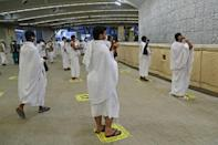 Pilgrims observing social distancing requirements at last year's hajj throw pebbles as part of the symbolic al-A'qabah (stoning of the devil ritual)