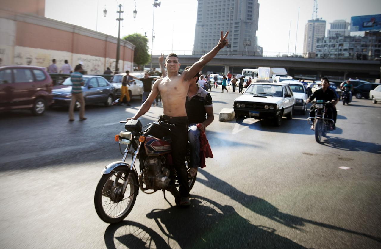 An Egyptian protester flashes the victory sign as he celebrates the victory of Mohammed Morsi of the presidential election in Tahrir square in Cairo, Egypt, Sunday, June 24, 2012. Mohammed Morsi was declared Egypt's first Islamist president on Sunday after the freest elections in the country's history, narrowly defeating Hosni Mubarak's last Prime Minister Ahmed Shafiq in a race that raised political tensions in Egypt to a fever pitch. (AP Photo/Mohammed Abu Zaid)