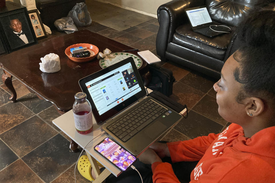 "Kristen King, 17, a junior at Americus-Sumter High School, in Americus, Ga., sits on her living room couch, attending school via a Chromebook propped on a TV tray, in Americus, Ga., March 1, 2021. ""It's been challenging,"" Kristen said. ""I like hands-on help from my teachers. We can't really see our friends, like our school friends. We can't really socialize with them. We can't really do anything."" (AP Photo/Jeff Amy)"