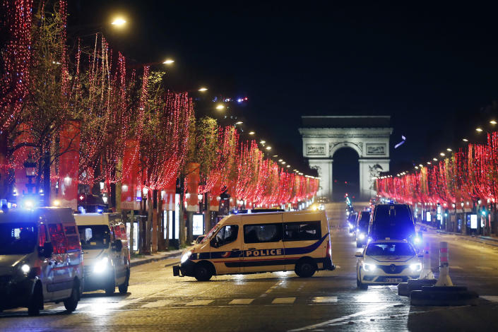 Police vans are parked on the Champs Elysees avenue during the New Year's Eve, in Paris, Thursday, Dec. 31, 2020. As the world says goodbye to 2020, there will be countdowns and live performances, but no massed jubilant crowds in traditional gathering spots like the Champs Elysees in Paris and New York City's Times Square this New Year's Eve. (AP Photo/Thibault Camus)