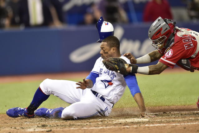 Toronto Blue Jays' Curtis Granderson (18) is tagged out at home by Los Angeles Angels catcher Martin Maldonado during the ninth inning of a baseball game in Toronto on Wednesday, May 23, 2018. (Frank Gunn/The Canadian Press via AP)