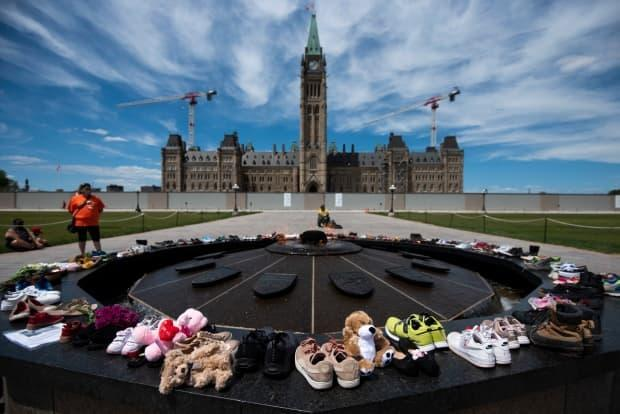 Shoes line the edge of the Centennial Flame on Parliament Hill on May 30, 2021, in memory of the children whose remains were found at the grounds of the former Kamloops Indian Residential School at Tk'emlups te Secwépemc First Nation in Kamloops, B.C. (Justin Tang/The Canadian Press - image credit)