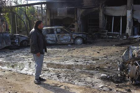 A man looks at the site of car bomb attack in Buhriz, 60 km (35 miles) northeast of Baghdad December 9, 2013. REUTERS/Mohammed Adnan
