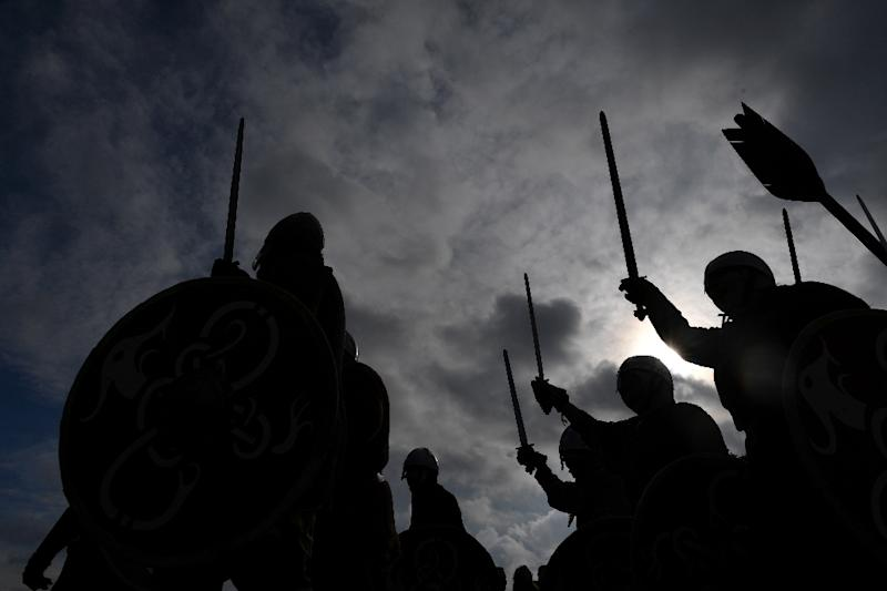 Re-enactors raise their swords as they take part in the re-enactment of the Battle of Hastings in southern England, on October 15, 2016 (AFP Photo/Ben Stansall)