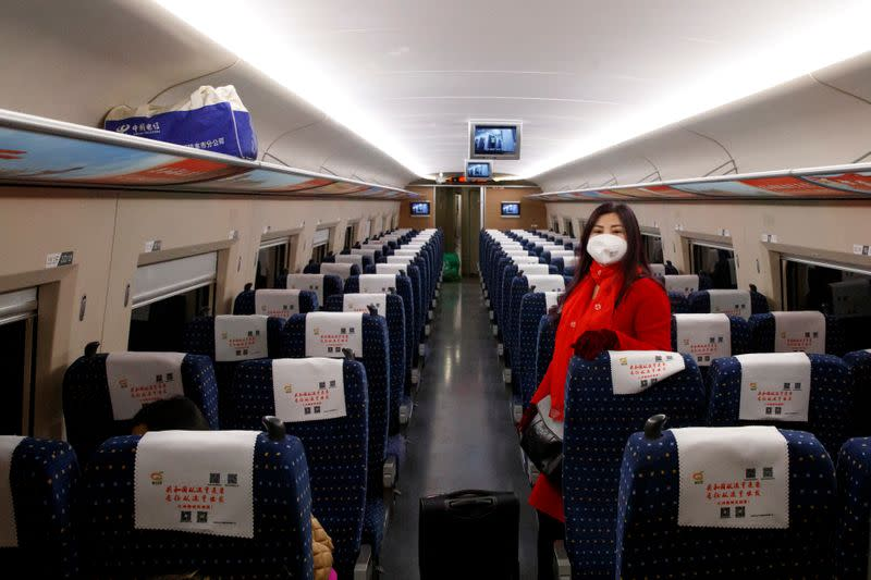 A woman wears a face masks as she travels on a high-speed train near Jiujiang