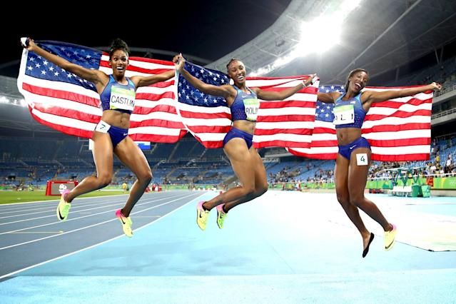 <p>(L-R) Bronze medalist Kristi Castlin, gold medalist Brianna Rollins and silver medalist Nia Ali of the United States celebrate with American flags after the Women's 100m Hurdles Final on Day 12 of the Rio 2016 Olympic Games at the Olympic Stadium on August 17, 2016 in Rio de Janeiro, Brazil. (Photo by Cameron Spencer/Getty Images) </p>