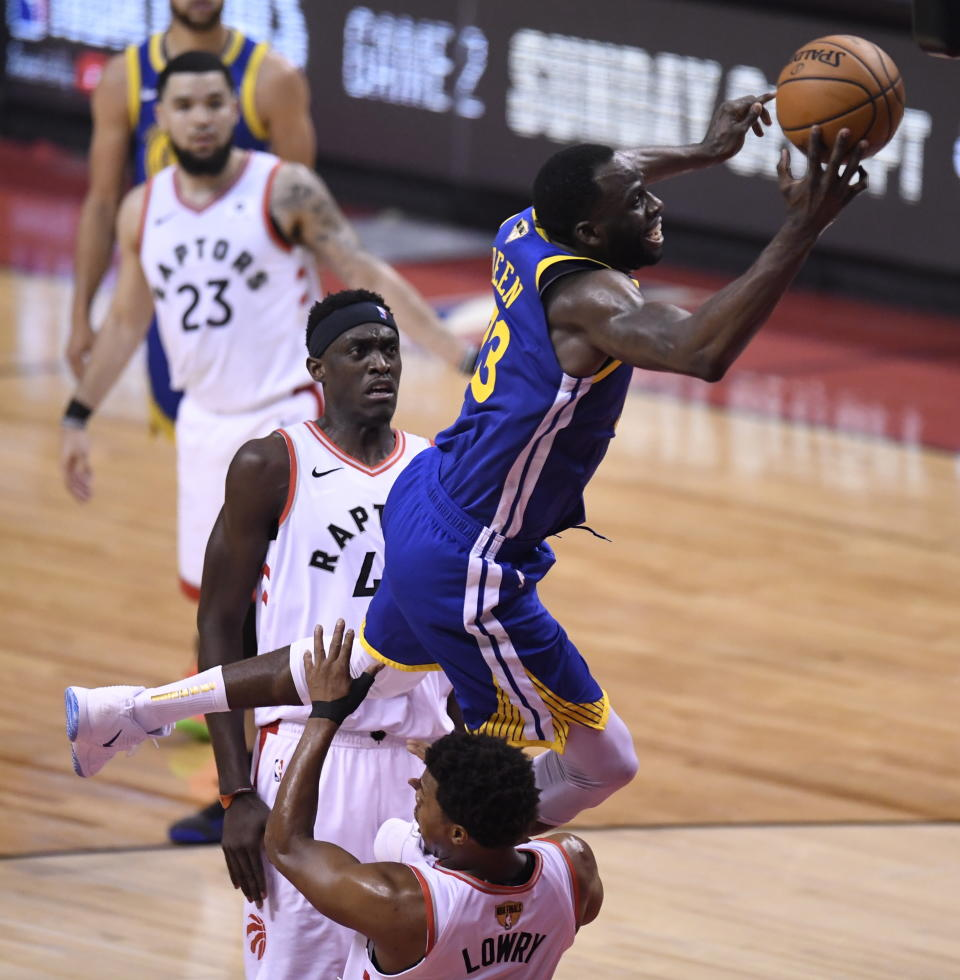 Golden State Warriors forward Draymond Green (23) commits an offensive foul on Toronto Raptors guard Kyle Lowry (7) during the first half of Game 1 of basketball's NBA Finals, Thursday, May 30, 2019, in Toronto. (Frank gunn/The Canadian Press via AP)