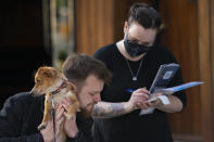 FILE - In this Monday, April 12, 2021 file photo, a customer holding his dog orders outside a restaurant in Liverpool, England. British Prime Minister Boris Johnson is expected to confirm Monday June 14, 2021, that the next planned relaxation of coronavirus restrictions in England will be delayed as a result of the spread of the delta variant first identified in India. (AP Photo Jon Super, File)