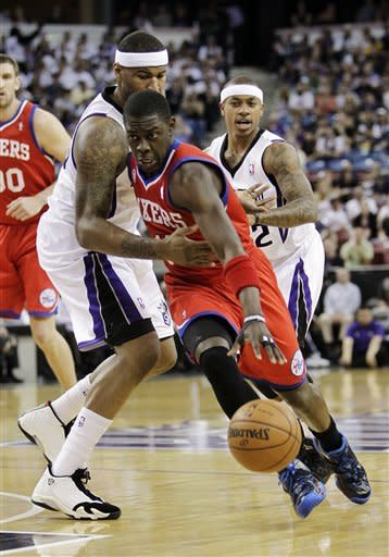 Sacramento Kings center DeMarcus Cousins, left, tries to stop the drive of Philadelphia 76ers guard Jrue Holiday during the first quarter of an NBA basketball game in Sacramento, Calif., Sunday, March 24, 2013. (AP Photo/Rich Pedroncelli)