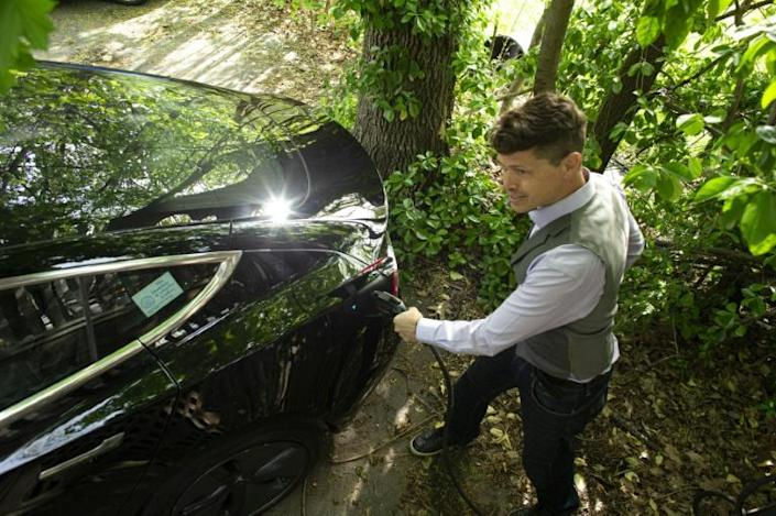 Ben Rich charges his Tesla vehicle in his backyard in Montclair, New Jersey on May 06, 2021. With more electrical models soon hitting showrooms, the focus will shift to consumer willingness to pivot to electric cars at a time when conventional gas stations remain familiar and ubiquitous.