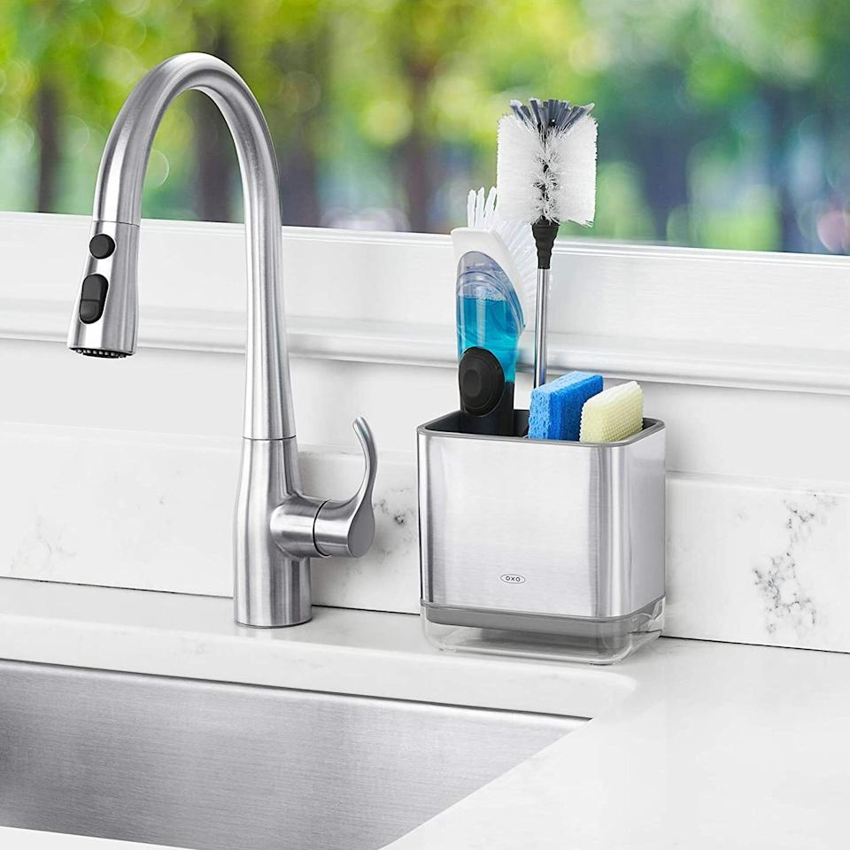 """Keep your favorite scrubbing tools in one neat place instead of strewn all over the sink. This caddy even has a handy drip tray so you can empty out any moisture.<br /><br /><strong>Promising review:</strong>""""I love all<a href=""""https://amzn.to/3aklxi1"""" target=""""_blank"""" rel=""""nofollow noopener noreferrer"""" data-skimlinks-tracking=""""5723569"""" data-vars-affiliate=""""Amazon"""" data-vars-href=""""https://www.amazon.com/stores/node/2598021011?_encoding=UTF8&field-lbr_brands_browse-bin=OXO&ref_=bl_dp_s_web_2598021011&tag=bfjasmin-20&ascsubtag=5723569%252C24%252C31%252Cmobile_web%252C1%252C0%252C14870725"""" data-vars-keywords=""""cleaning"""" data-vars-link-id=""""14870725"""" data-vars-price="""""""" data-vars-product-id=""""16621214"""" data-vars-retailers=""""Amazon"""">OXO products</a>and am also happy with this purchase. I place my dish sponges in this and there is enough room for a brush as well. I like also the vent insert which keeps the sponges separate. The compartment at the bottom is a great idea in the design to allow for emptying water rather than letting it pool at the bottom. It is a separate compartment which is of clear plastic and allows you to visibly see if it needs emptying. Great product. Very satisfied."""" —<a href=""""https://amzn.to/3e9tK9J"""" target=""""_blank"""" rel=""""nofollow noopener noreferrer"""" data-skimlinks-tracking=""""5723569"""" data-vars-affiliate=""""Amazon"""" data-vars-href=""""https://www.amazon.com/gp/customer-reviews/R29SY51ECYVJGM?tag=bfjasmin-20&ascsubtag=5723569%2C24%2C31%2Cmobile_web%2C0%2C0%2C0"""" data-vars-keywords=""""cleaning"""" data-vars-link-id=""""0"""" data-vars-price="""""""" data-vars-retailers=""""Amazon"""">Amazon Customer</a><br /><br /><strong>Get it from Amazon for <a href=""""https://amzn.to/2RFMuWW"""" target=""""_blank"""" rel=""""noopener noreferrer"""">$13.99</a> (available in two colors).</strong>"""