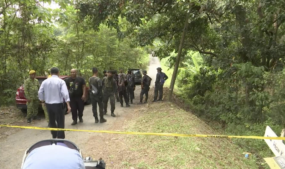 In this image from a video, rescuers gather in the cordoned off area in Pantai, Malaysia Tuesday, Aug. 13, 2019. Malaysian rescuers on Tuesday found the body of a Caucasian female in the forest surrounding a nature resort where a 15-year-old London girl was reported missing more than a week ago, police said. State police chief said officials were in the process of determining whether the body is Nora Anne Quoirin, who was discovered missing by her family from the Dusun eco-resort in the southern state on Aug. 4. (AP Photo)