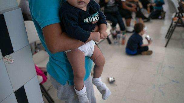 PHOTO: A young mother holds her infant after they arrived on an ICE deportation flight from Brownsville, Texas on Aug. 29, 2019, to Guatemala City. (John Moore/Getty Images)